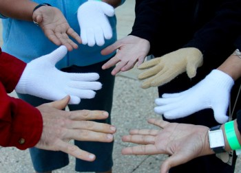 """Photo showing eight hands with varied skin tones: 4 with gloves, 4 without. By sharing three sets of """"emergency gloves"""" among the five of us, we found a way to share in the warmth: each of us with one hand covered, one uncovered. Together, we created some warmth, much laughter, and good memories that remind me still today that we need solutions for solidarity and mutual support. Together, we can create warmth, even in chilly conditions."""