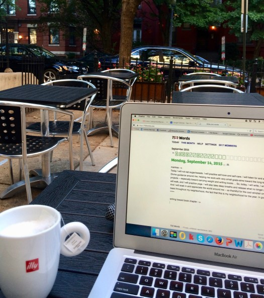 Image from an outdoor café. In the foreground are a vegan tea latte and laptop open to the writing website 750words.com. In the background appear metal chairs and tables inside a metal fence. Beyond the café are cars, trees, and row houses.