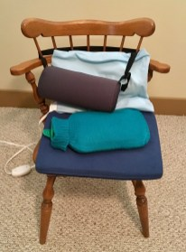 A wooden chair I use for writing with support cushions (a wedge and lumbar roll), heating pad, and hot water bottle: all in shades of blue (blue being associated with the 5th chakra and communication).