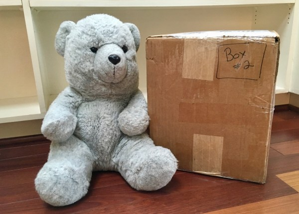 A grey teddy bear sits next to a cardboard box, which is full of books.