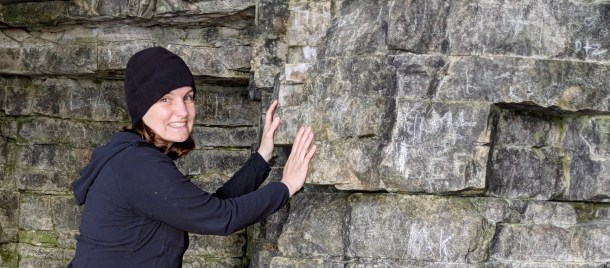 Here Beth is wearing a black fleece hat and jacket and pressing hands into a rock wall that stretches outward to the right.