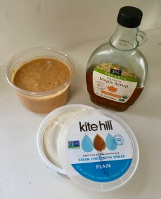 This photo shows the 3 ingredients for making sweet spread: (1) peanut butter (freshly ground without labeling) in the upper left; (2) vegan cream cheese (this one by Kite Hill) in the lower center; and (3) maple syrup (a bottle with 365 label) in the upper right.