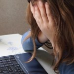 This image shows a person (read as a white woman) with hands and hair covering the face and whole body slumped in front of an open laptop.
