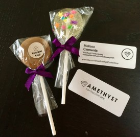 This photo shows two lollipops—coconut chai caramel and lemon with sprinkles—alongside cards for Amethyst Confections.