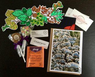 """Sample thank-you package contents, including a homemade card and bookmark, tea for """"positive energy,"""" and vegan + gluten-free candy from Amethyst Confections."""