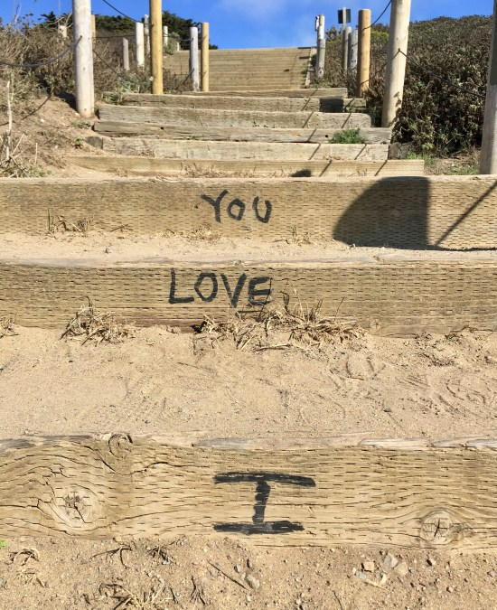 """This image, taken near the coast in San Francisco, shows the words """"I LOVE YOU"""" written in black marker on tan wooden planks: part a staircase partially covered in sand."""