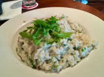 Creamy risotto with peas and mushrooms, topped with arugula/rocket.