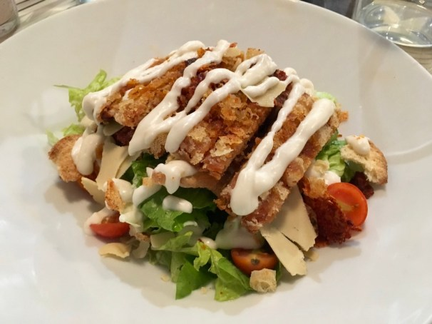 This Caesar salad is topped with slices of vegan cheese, crispy tempeh strips, and a creamy salad dressing.