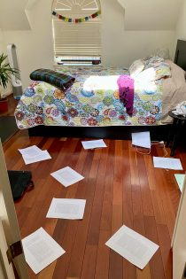 This photo shows scattered papers (page proofs) across a wooden floor in a bedroom—with a colorful bedspread, pillows, blanket, sweater, plant, air purifier, bedside table, books, window, and white walls all part of the scene.