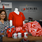 This image shows Ileana Rodriguez standing next to UW-Madison Badger clothing and mugs (all red and white) inside Scrubs Station in Madison, Wisconsin.