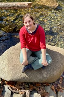 This photo shows Beth Godbee, Ph.D. -- sitting on a rock surrounded by reflective water, leaves, and rocks. Photo taken at White Oaks Canyon in Shenandoah National Park (in the Appalachian Mountains).