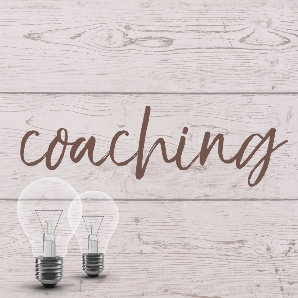 "This button reads ""coaching"" and shows two light bulbs against a light pink wood planked background."