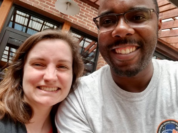 This selfie shows Beth Godbee on the left and Cedric Burrows on the right: both smiling—positioned in front of a brick building and glass windows reflecting steel beams.