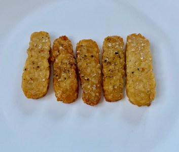 Vegan and gluten-free tempeh sticks appear in a row of five, side-by-side, brown and crispy.