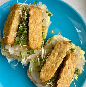 Tempeh sticks cover open-faced sandwiches of mashed avocado, sour kraut, and microgreens and on ciabatta buns.