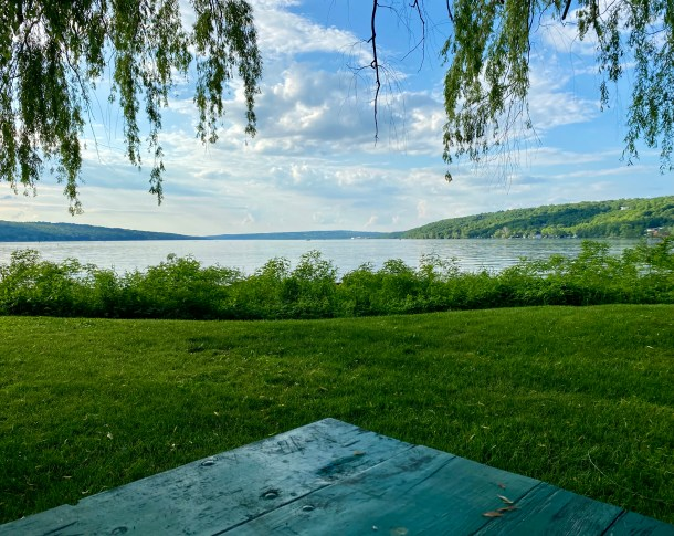 This photo shows a late summer afternoon. The corner of a green picnic table points toward a green field and blue lake stretching out to blue-green hills. Leaves hang down, and puffy white-grey clouds float overhead. The scene, hopefully, captures the possibilities of summer: open, outdoor space inviting contemplative practices.
