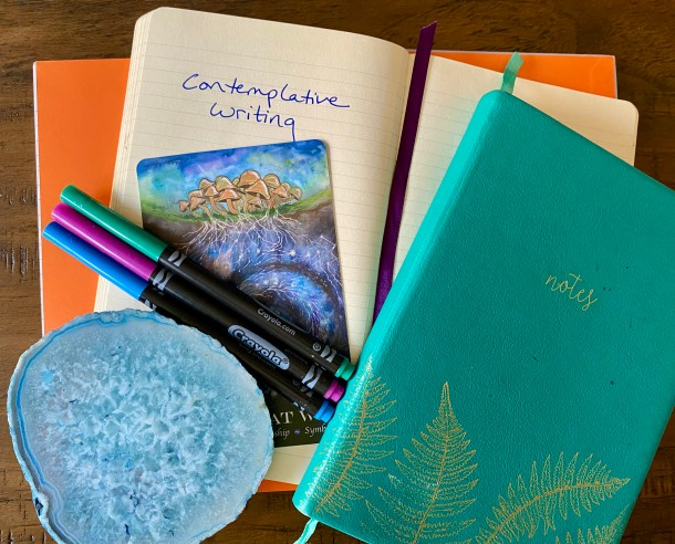 """This photo shows multiple journals, open to a lined notebook page that says """"contemplative writing."""" A colorful divination card, blue crystal, and three markers sit on top of the journals."""