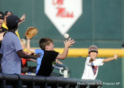 boy catching ball with eyes closed