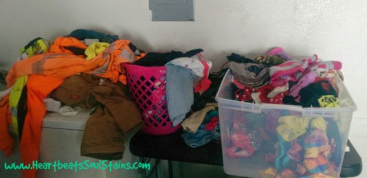 Piled dirty clothes in my crazy chaotic laundry room