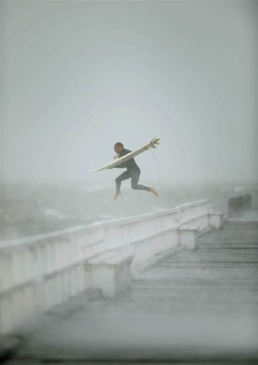 A surfer won't let the adversity of a storm stop him from hitting the waves