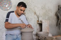 A moroccan doing pottery at a pottery workshop.