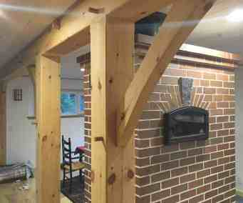 timbered carrying beam flanking masonry heater in custom home designed by Homestead Heat