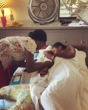 Haitian midwife helps new mother and baby with breastfeeding at Heartline Maternity Center.