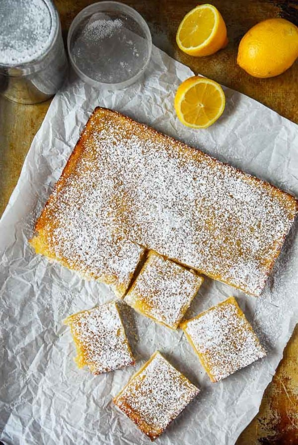 vegan lemon bars on parchment paper with lemons