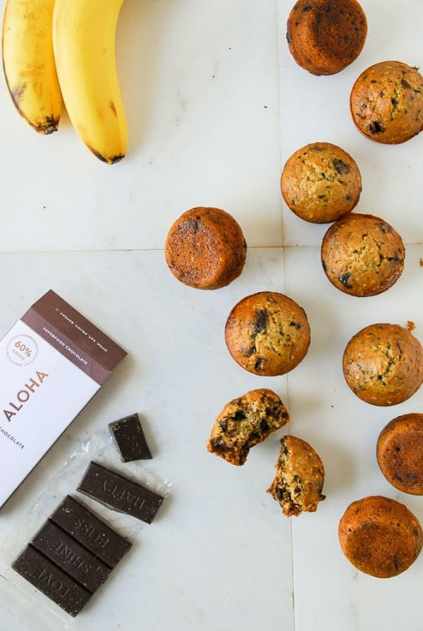 Banana and dark chocolate steel cut oat muffins on a marble background with bananas