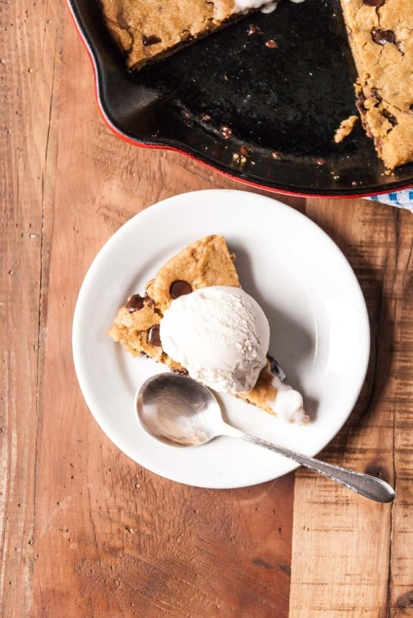 slice of chocolate chip skillet cookie with a scoop of ice cream