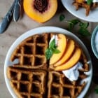Vegan + Gluten Free Peach Waffles with Mint Coconut Whipped Cream- Perfectly crispy vegan and gluten free peach waffles, topped with vegan mint coconut whipped cream and fresh peaches!