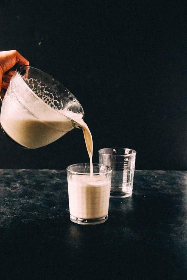 pouring homemade cashew milk into a glass