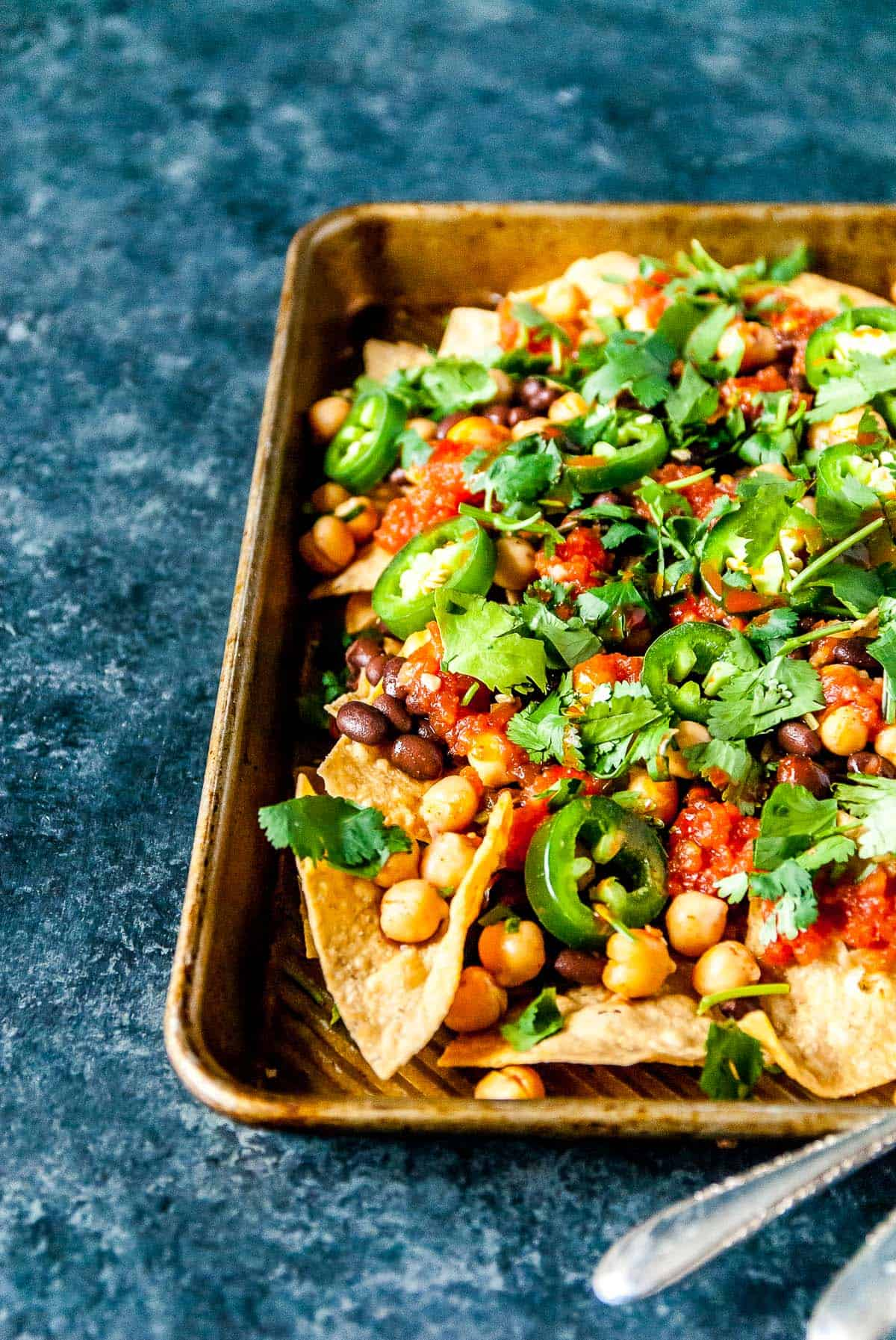 The ultimate vegan nachos, loaded with black beans, spicy chickpeas, and all your favorite toppings! These are a winner for your next party, potluck, or family dinner.