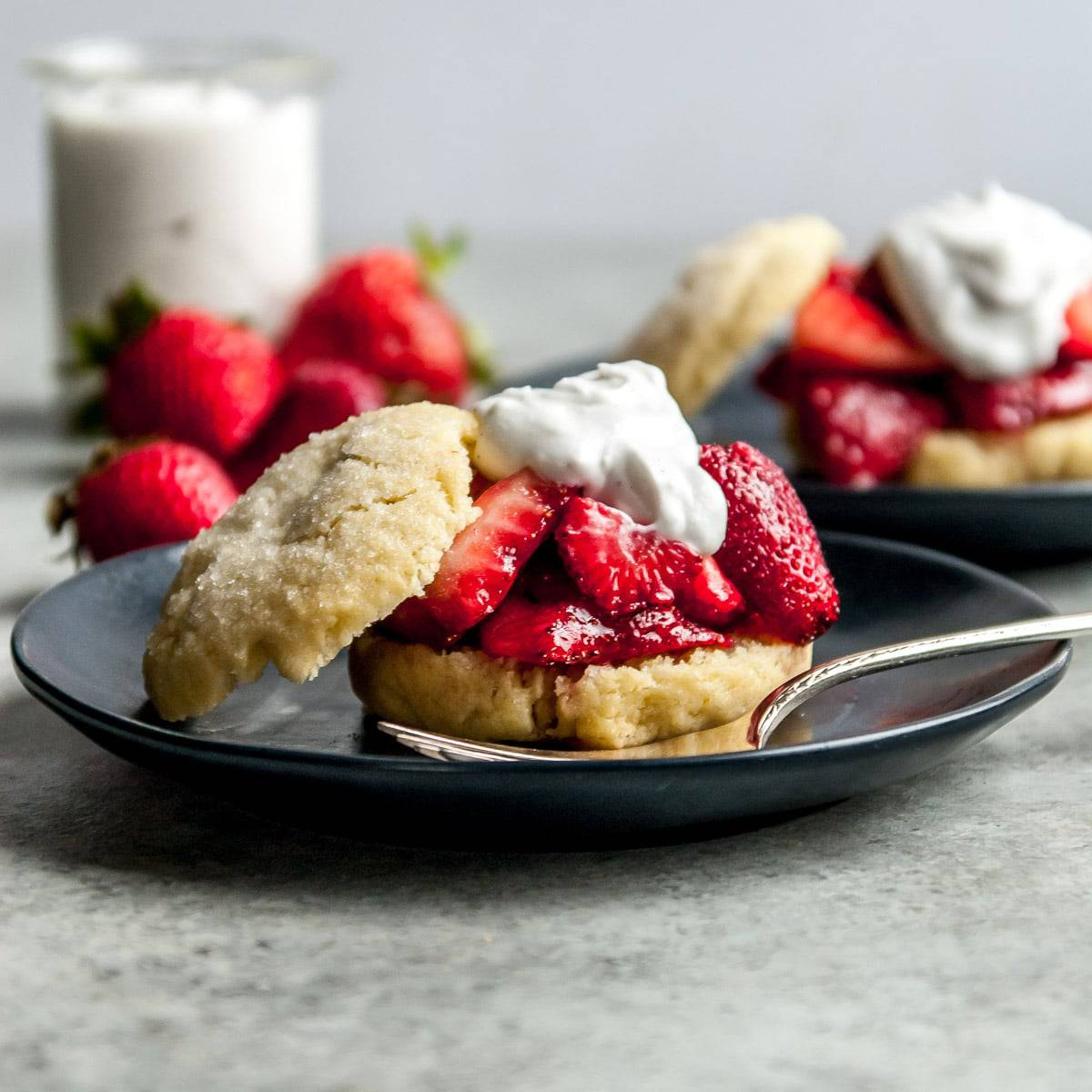 strawberry shortcake on a plate with a fork and whipped coconut cream in the background
