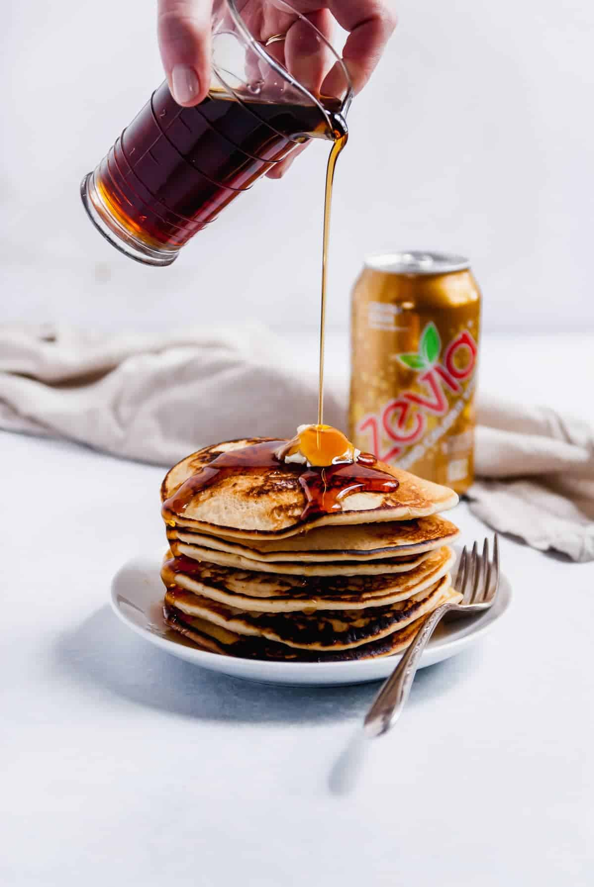 pancakes on a plate with syrup being poured onto them