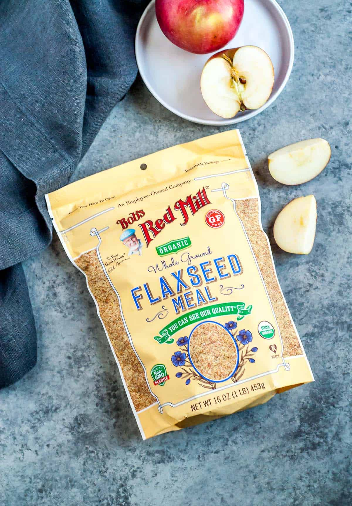 bag of flaxseed meal on a blue background with apple