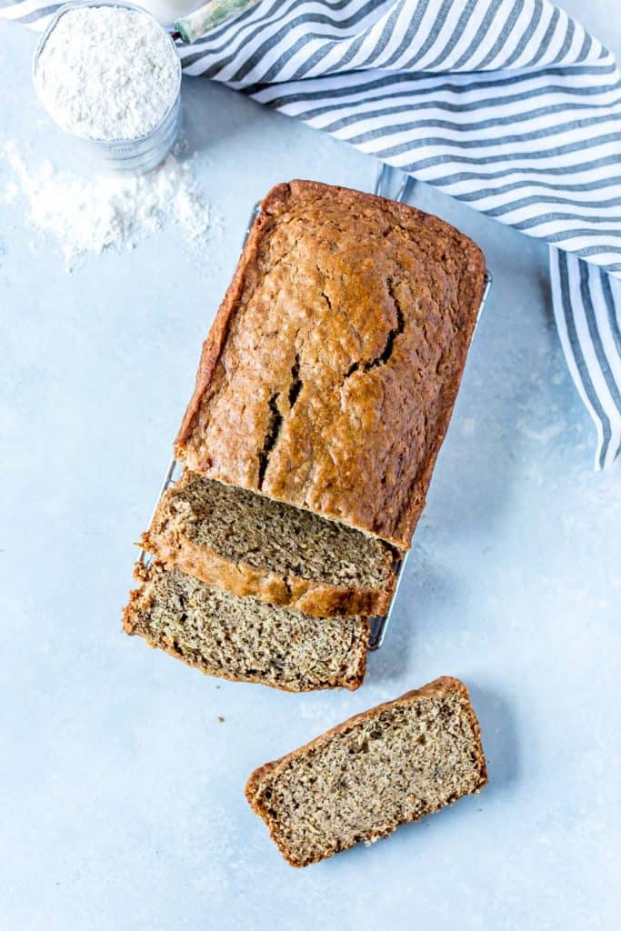 Overhead of banana bread with a cup of flour and striped napkin
