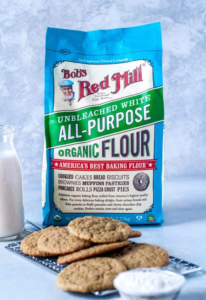 Bag of flour with pile of ginger cookies and glass of milk