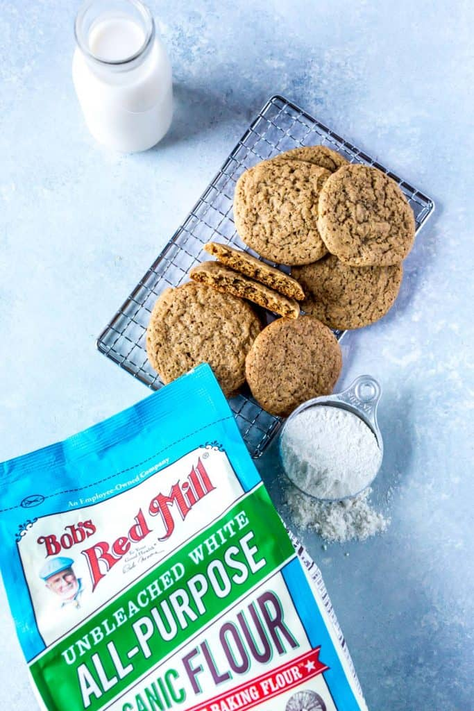 pile of ginger cookies with cup of flour and bag of flour on blue background