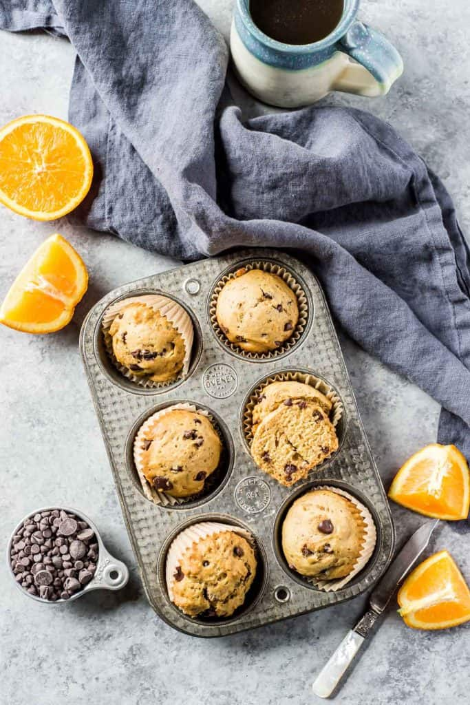 muffins in tin with oranges and chocolate chips