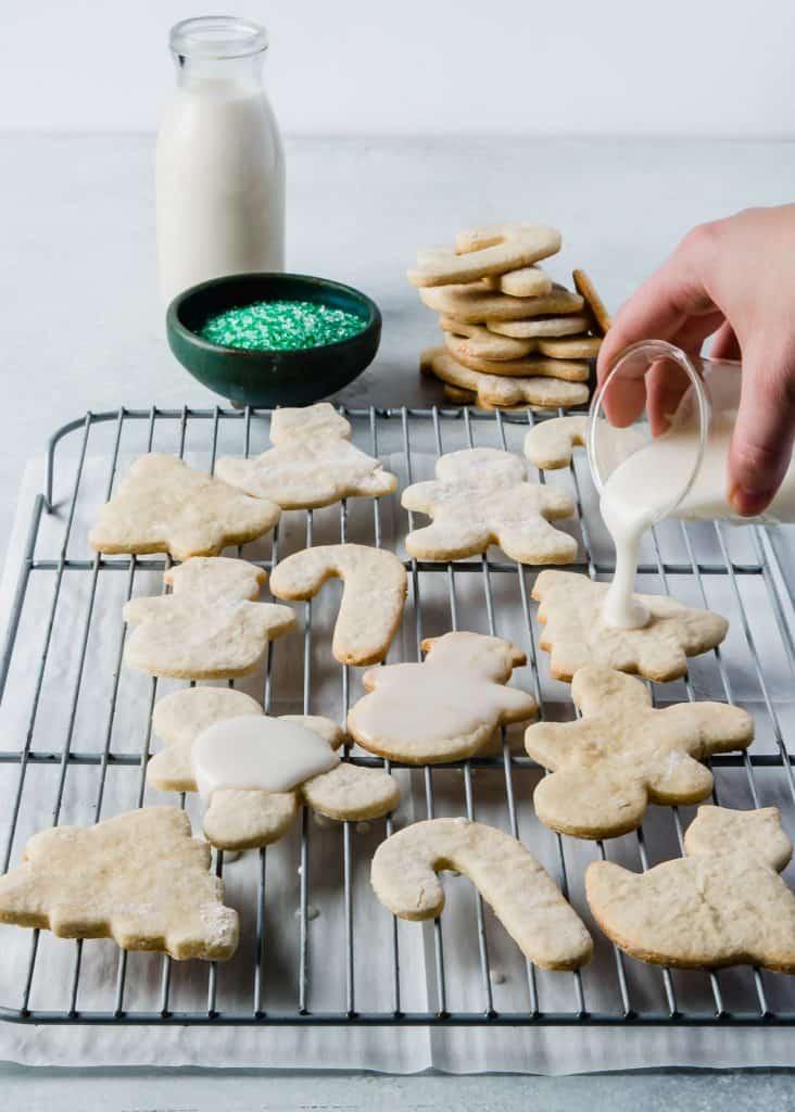 Frosting being poured on vegan sugar cookie