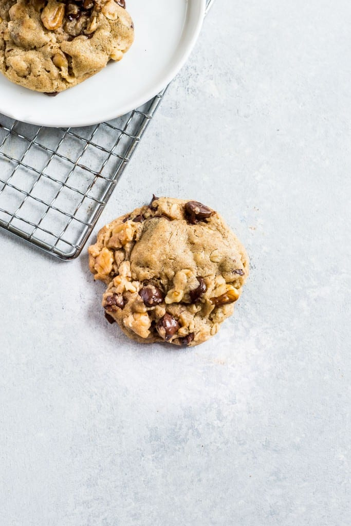Chocolate chip cookies on a white plate with a blue background
