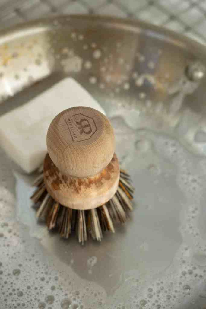 dish brush with bar soap scrubbing a pan