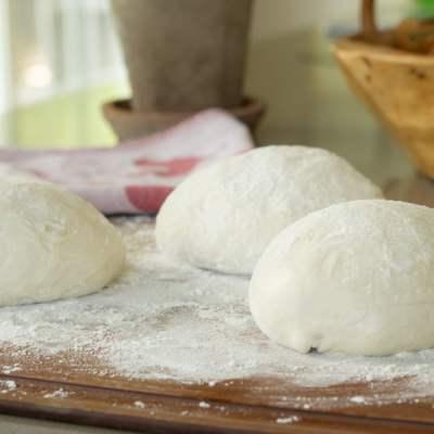 3 pizza dough balls on counter