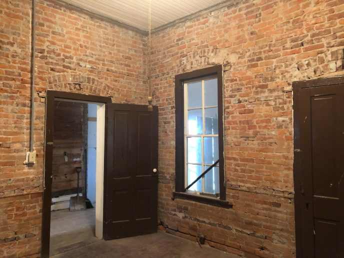 This is in the room behind the fancy front room. You can tell from the brick that the door to this room was originally its current size. The door to the icky bathroom, at right, must have been an exterior door.