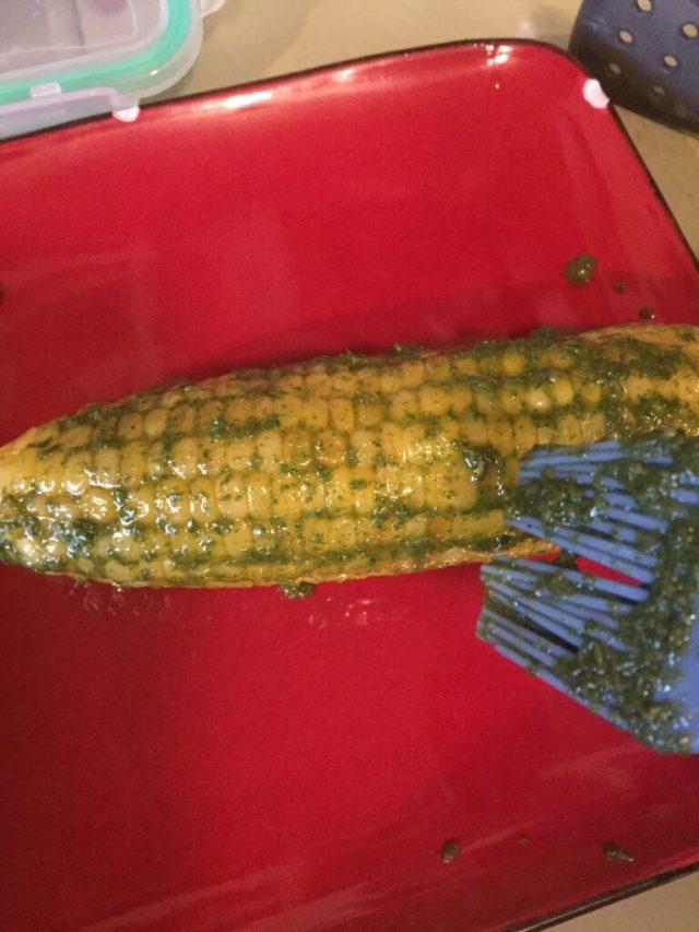 Brushing more pesto on corn on cob