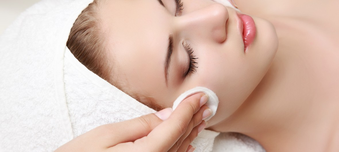 Woman gets face cleansed in preparation for a facial at spa.