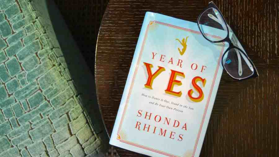 Year of Yes book on table with glasses.