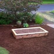 Wooden raised bed in front yard of house.