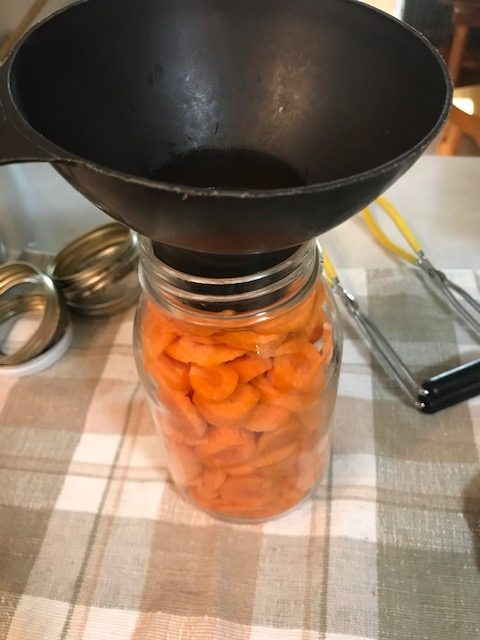 filling a quart jar with carrots